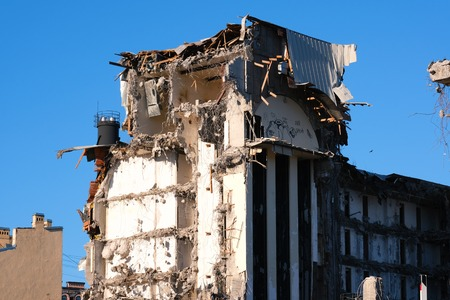 Demolished destructed building ruins. Demolition site in european city. Ruined house on a bright blue sky on a sunny day.
