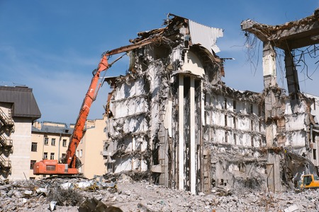 Building demolition with hydraulic excavator. Dismantle of destructed house ruins at bright sunny day with clear blue sky.