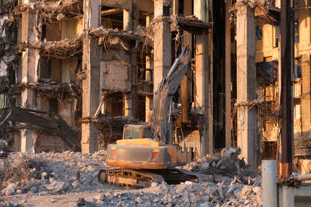 Building demolition with hydraulic excavator. Dismantle of destructed house ruins at bright sunsest Imagens