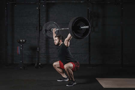 Young cross fit athlete doing squats with barbell over head. Man practicing functional training. Powerlifting workout exercises Stock Photo