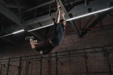 Young crossfit athlete swinging on gymnastic rings doing pull-ups at the gym. Workout exercises