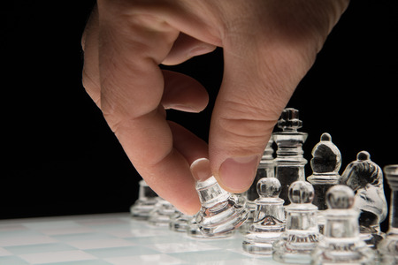 Hand holding the  pawn to make the first move photo