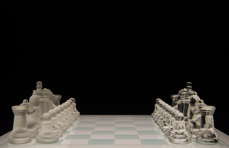 Glass chess board isolated on black photo
