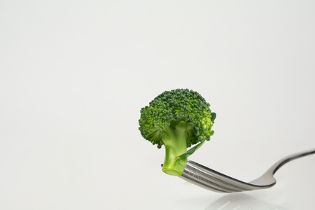 mouthful: Fresh green broccoli on fork isolated on white