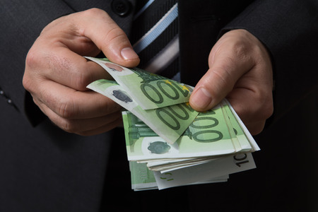 cash on hand: Man in black suit counts euro money