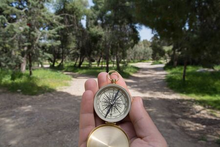 Compass being held out to determine direction photo