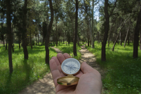 forked road: Compass being held out to determine direction Stock Photo