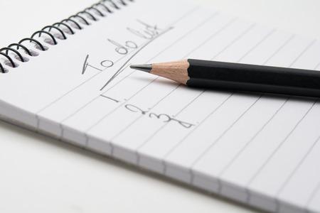hacer: Primer plano de un lápiz y un bloc de notas