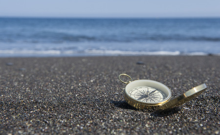Golden compass on the seashore. Focus on compass