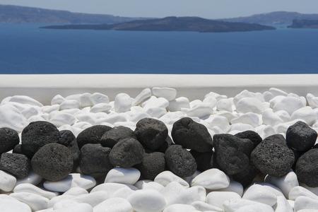 volcanic stones: Black volcanic stones over white. Decoration detail at Santorini, Greece.