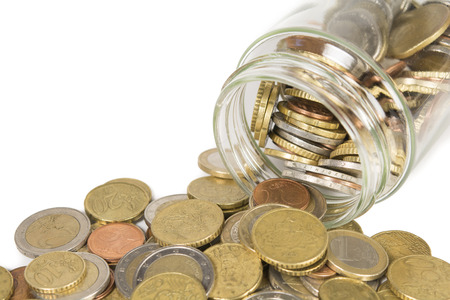 spilling: euro coins, spilling out of a jar. Isolated on white Stock Photo