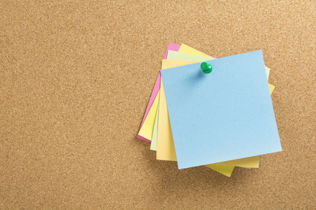 colored notepapers with green push pin on a corkboard