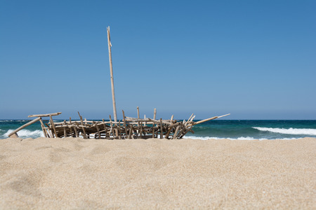 Boat with a mast made of reeds on the sand by the sea