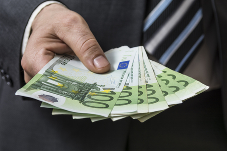 Businessman in grey suit giving euros, shallow depth of field