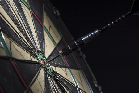 Dart in bulls eye of dartboard, close up