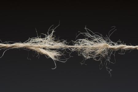 Frayed rope ready to break on dark background