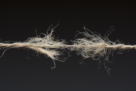 Frayed rope ready to break on dark background