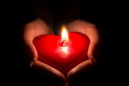 womans hands holding a heart shaped candle in the dark Stock Photo