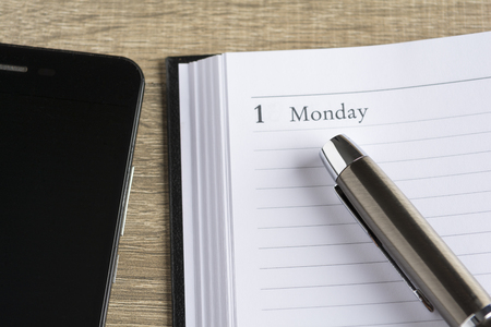 notebook: ?etal pen on a calendar with the page showing the first day of the monthweek and a smartphone in a setting goals concept Stock Photo