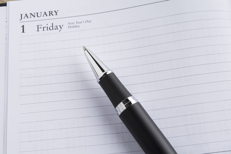 notebook: Metal pen on a calendar with the page showing the first day of the year in a setting goals concept