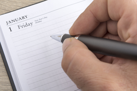 notebook: Mans hand holds a metal pen ready to set goals for the new year Stock Photo
