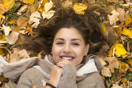 Smiling sweet girl lies down over autumn leaves