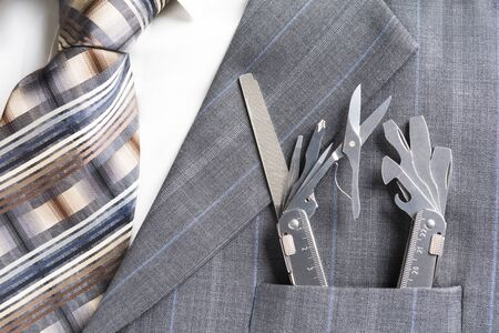 Multitool in pocket of businessman in a supportservice concept Standard-Bild