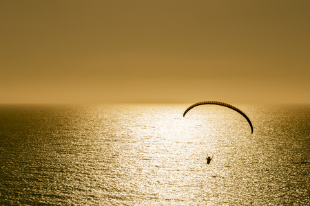 Silhouette of paraglider flying at sunset over the sea