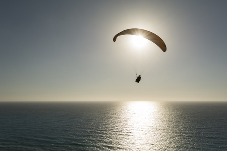 Silhouette of paraglider flying against sky