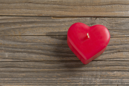 Red heart shaped candle on a wooden surface