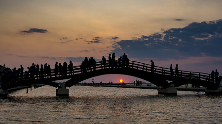 Tourist silhouettes stand on the bridge and gaze at the sunset Standard-Bild