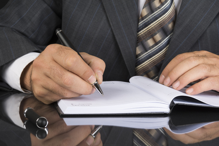 Man in gray suit holds a metal pen and is ready to write on a personal planner organizer