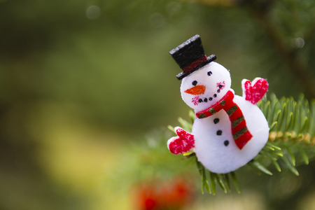 Snowman, christmas ornament hanging on a pine tree outdoors