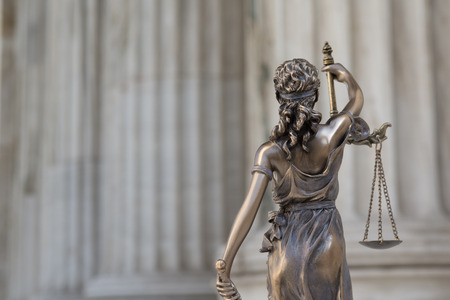 The statue of justice Themis or Iustitia, the blindfolded goddess of justice against an ionic order colonnade, as a legal concept