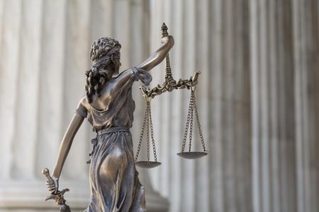 Het standbeeld van rechtvaardigheid Themis of Iustitia, de geblinddoekte godin van gerechtigheid tegen een colonnade van de ionische orde, als een juridisch concept