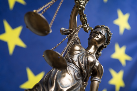 Statue of the blindfolded goddess of justice Themis or Justitia, against an european flag, as a legal concept