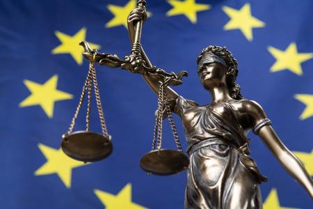 Estatua de la diosa de la justicia con los ojos vendados Themis o Justitia, contra una bandera europea, como concepto legal Foto de archivo