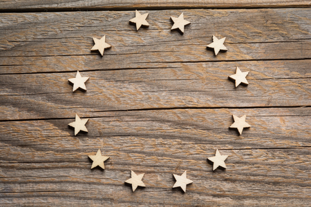 Twelve wooden craft stars form European's Union symbol on a wooden weathered surface