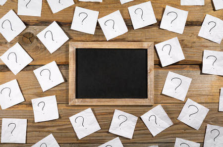 Question marks on crumpled note paper around a small blank blackboard on a wooden background
