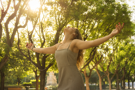 Carefree young attractive woman with her arms raised feeling free while listening music in the park
