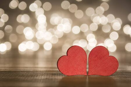 Two red hearts on wooden surface with bokeh lights background, on a valentines day concept