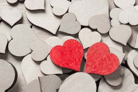 Two wooden painted red hearts among many colorless wooden hearts Stock Photo