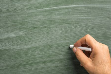Close up of man hand holding chalk against green chalkboard