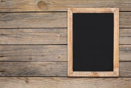 Small vintage blank chalkboard on an old wooden background Zdjęcie Seryjne