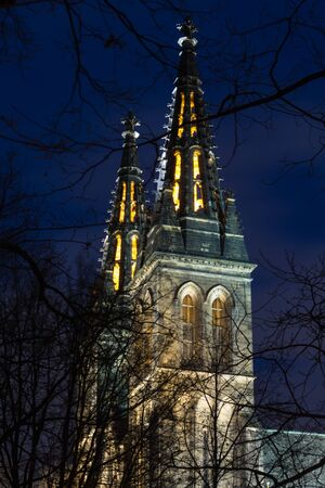 Illuminated towers of the neo gothic basilica of apostles Peter and Paul at Vysehrad castle in Prague at night