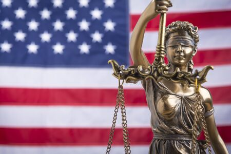The statue of justice Themis or Justitia, the blindfolded goddess of justice against a flag of the United States of America, as a legal concept Standard-Bild