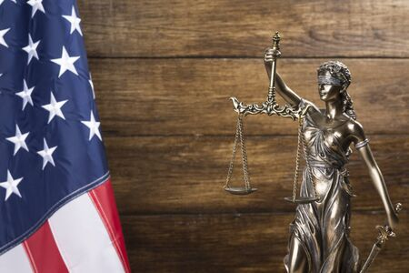 The statue of justice Themis or Justitia, the blindfolded goddess of justice against a flag of the United States of America, as a legal concept