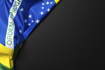 Brazilian flag lying on black grainy background