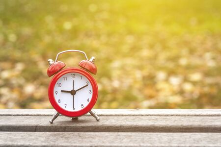 Red retro clock on a wooden table and blurred fallen leaves