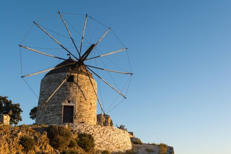 Traditional old stone windmill, iconic building located on all Greek islands Standard-Bild - 145769835